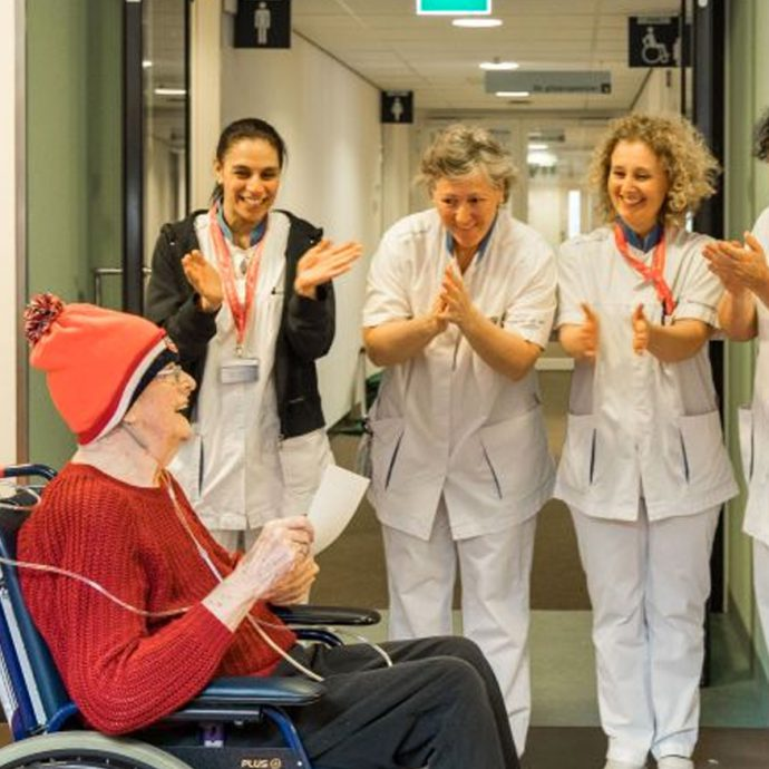 Foto van Patiënt met Unox muts in rolstoel