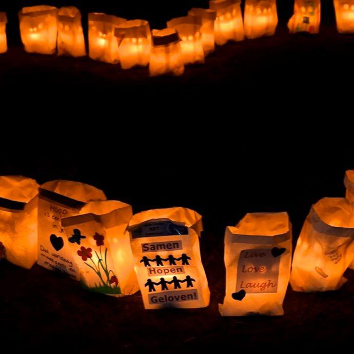 Foto van een als hart gerangschikt veld met verlichtte kaarstassen